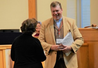 Moderator Ed Johnson passes gavel to new moderator Lisa Hebacker