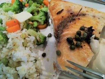swordfish steak with capers, served with a white sauce, rice and mixed veggies